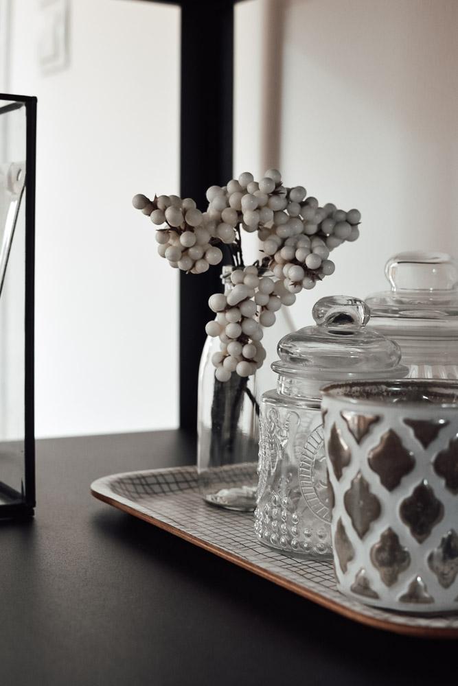 kleine Vase und Teelichter als Gruppe sortiert im offenen Regal