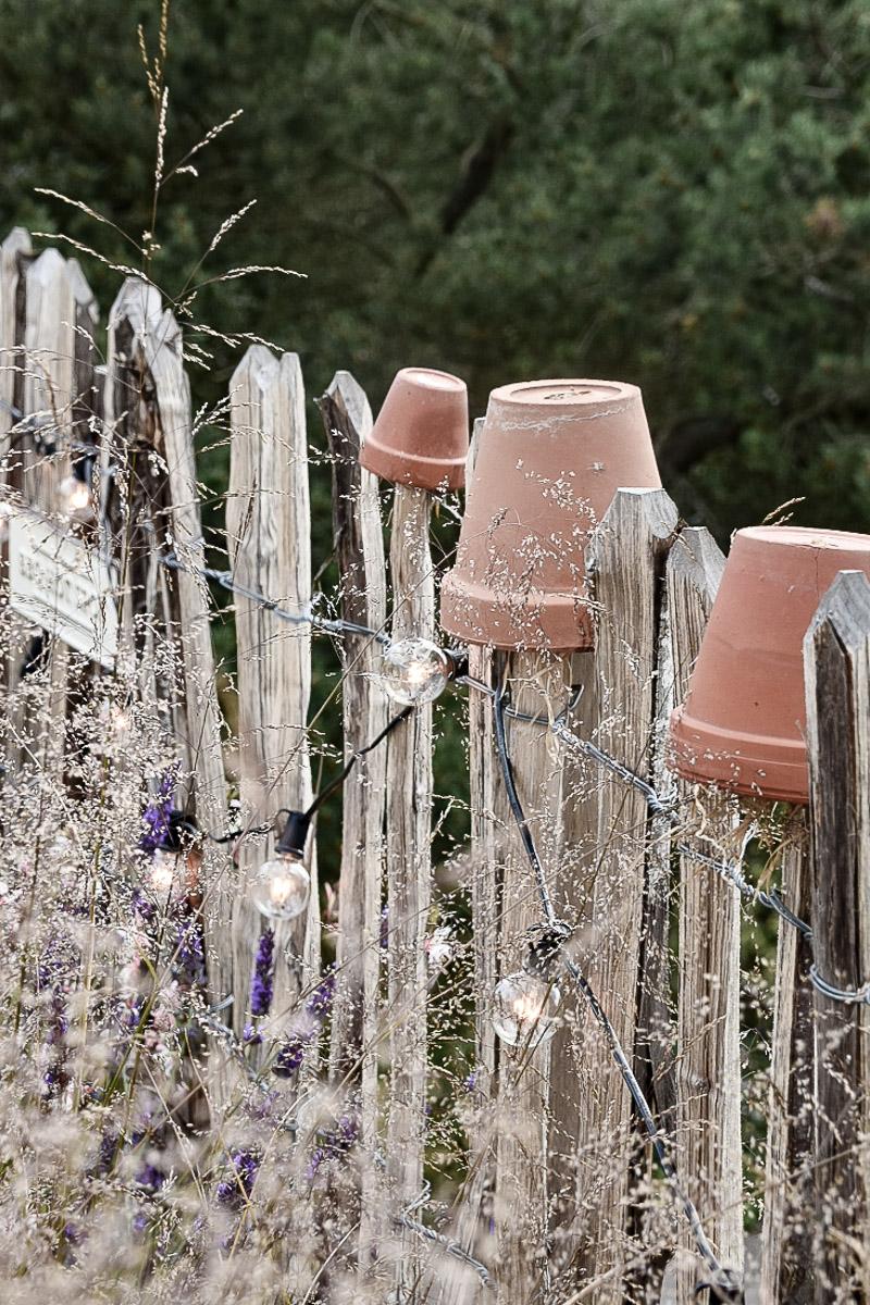 Insektenhotel an Staketenzaun im naturnahen Garten